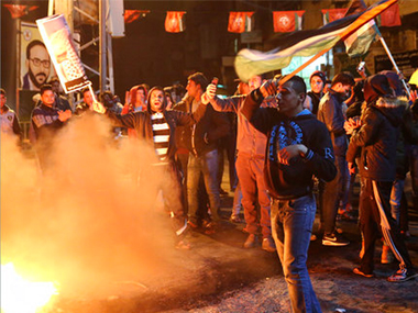 Palestinian protestors burn tires as they wave national flags during a protest at the main Square in Gaza City on Wednesday. AP