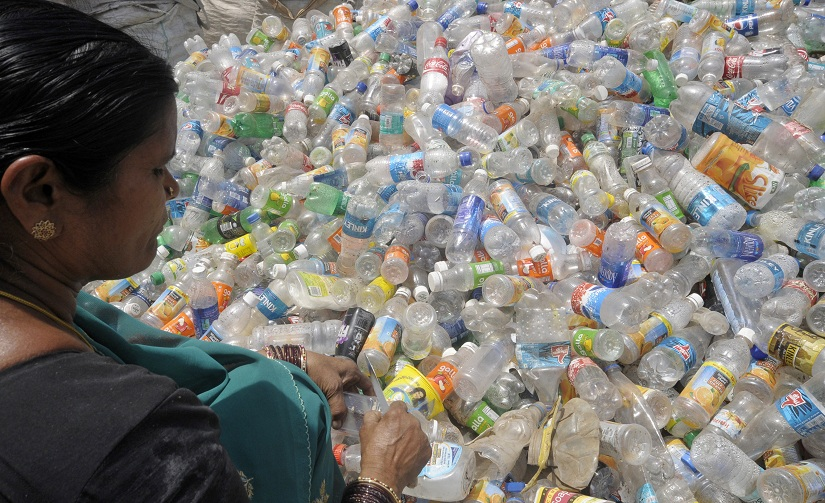 A worker removes labels from plastic bottles inside a plastic recycling unit in the southern Indian city of Hyderabad May 12, 2011. It has been estimated that India generates around 5600 tonnes of plastic waste daily, manager of the unit said on Thursday. REUTERS/Krishnendu Halder (INDIA - Tags: BUSINESS) - GM1E75C1KAR01