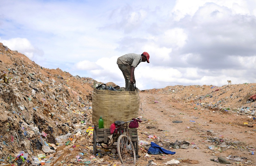 A rag picker prepares to pack a sack filled with recyclable materials, mounted on his tricycle at a garbage dump on the outskirts of the southern Indian city of Bangalore August 26, 2014. REUTERS/Abhishek N. Chinnappa (INDIA - Tags: ENVIRONMENT SOCIETY) - GM1EA8Q1PUU01
