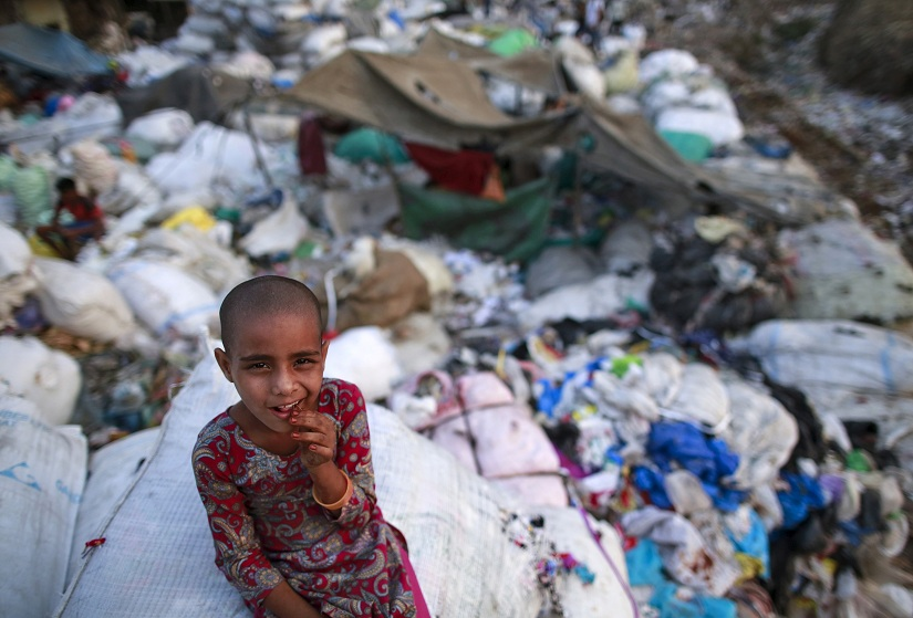 A girl sits on a sack of discarded clothes at a slum in Mumbai, India, April 20, 2016. REUTERS/Danish Siddiqui TPX IMAGES OF THE DAY - GF10000389763