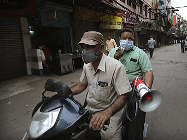 Civil defense volunteers on a scooter ask people to go inside their houses during a lockdown to control coronavirus spread in New Delhi. AP