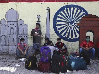 Migrant workers wait outside a railway station hoping to be able to return to their home states, in Mumbai. AP