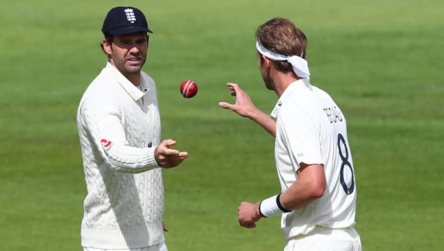 England's James Anderson, left, passes the ball to teammate Stuart Broad during the fifth day of the third cricket Test match between England and West Indies at Old Trafford in Manchester, England, Tuesday, July 28, 2020. (Michael Steele/Pool via AP)