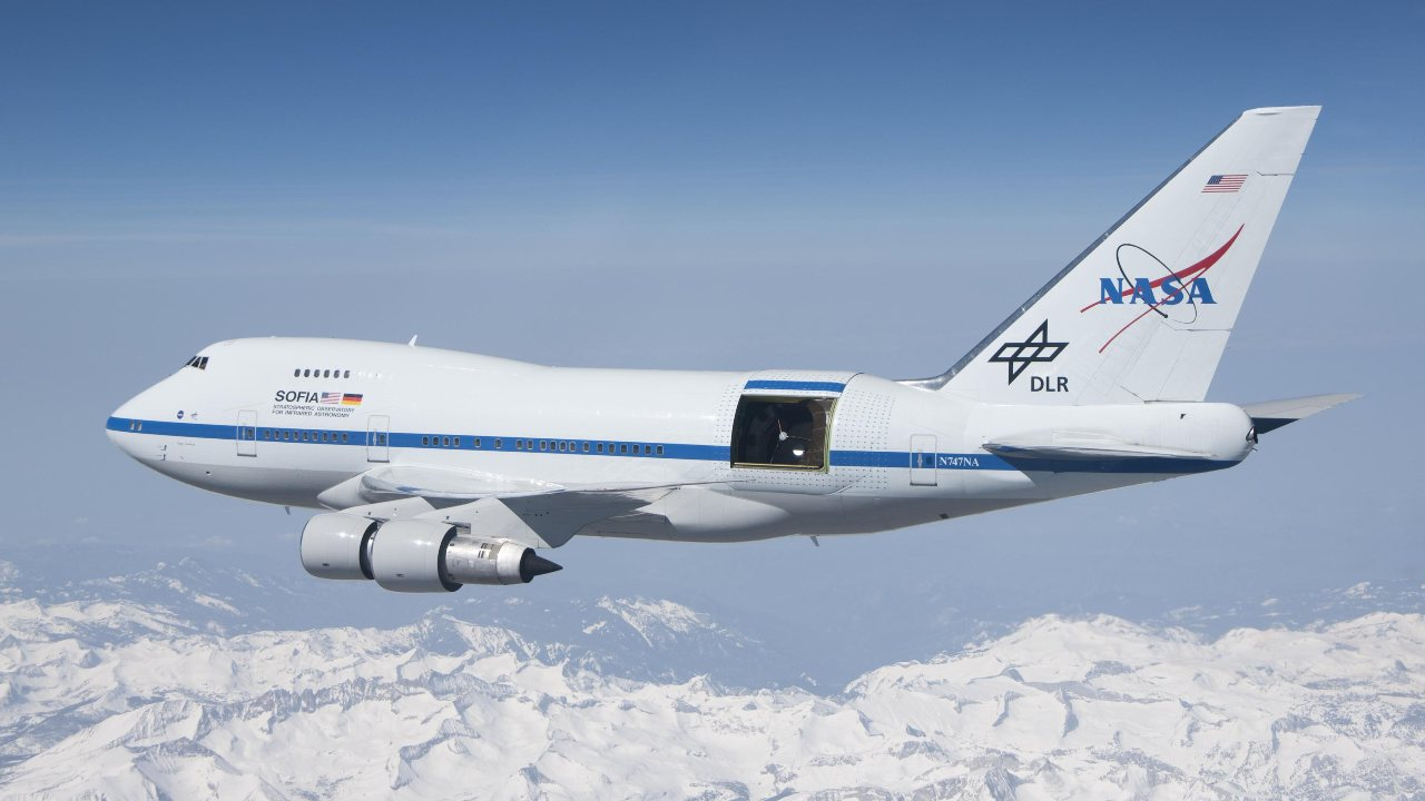 SOFIA soars over the snow-covered Sierra Nevada mountains with its telescope door open during a test flight. SOFIA is a modified Boeing 747SP aircraft. Image Credits: NASA/Jim Ross