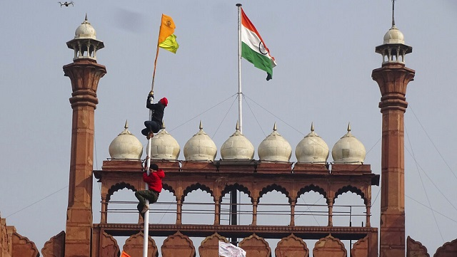 A Sikh man hangs on to pole holding a Sikh flag along with a farm union flag at the historic Red Fort. AP